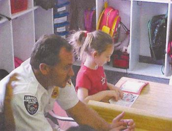 A child reads a book at the fire department.